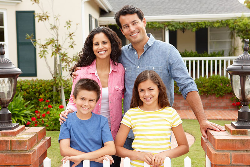 happy family posing in front of a white picket fence
